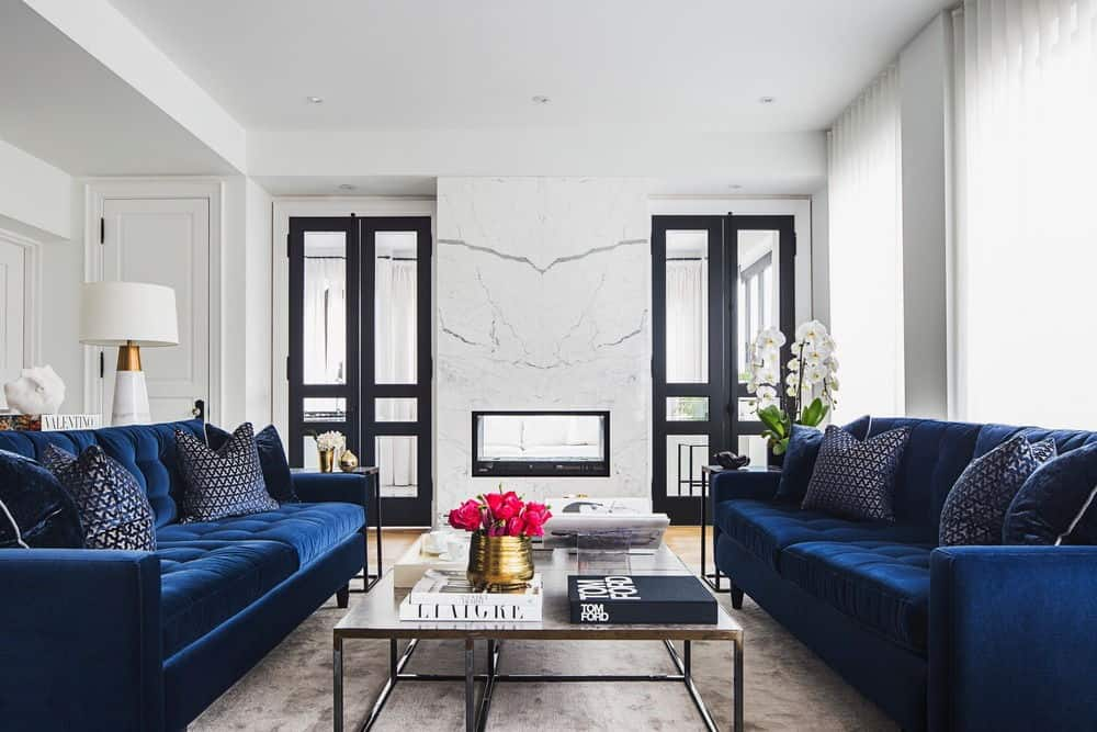 Gorgeous living room features velvet royal blue sofas facing each other with a metal coffee table in between.