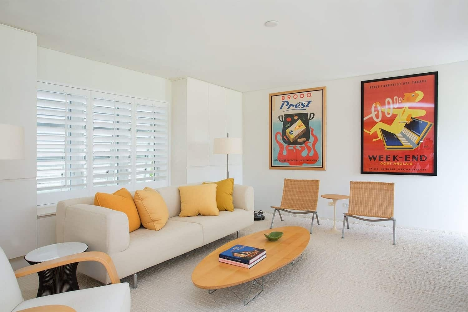 White living room styled with artwork frames and orange pillows that lay on a beige sofa. It is paired with an oval coffee table along with white and rattan chairs.
