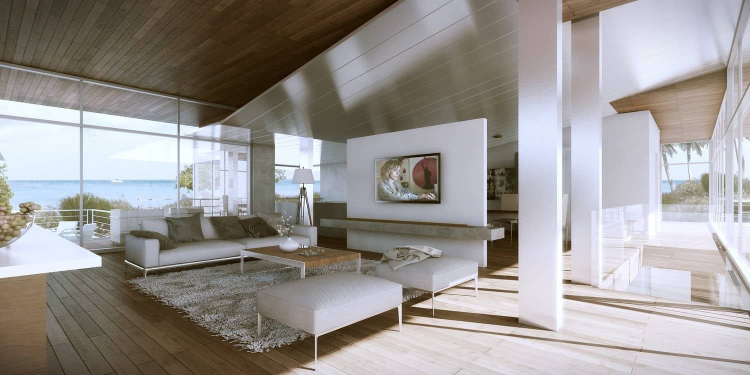 Modern living room with a natural wood plank flooring and vaulted ceiling. It also has floor to ceiling glass windows overlooking a serene beach view.