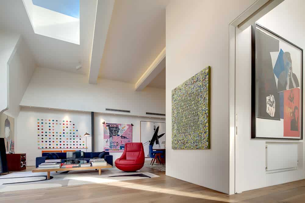 Fabulous living room showcases huge artworks mounted on the white walls. It has a navy blue sofa and red accent chair with an immense wooden coffee table.
