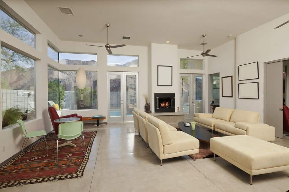 A modern fireplace fixed to the white wall below a blank canvas adds warmth to this living room. It has two sitting areas both with rugs and ceiling fans.