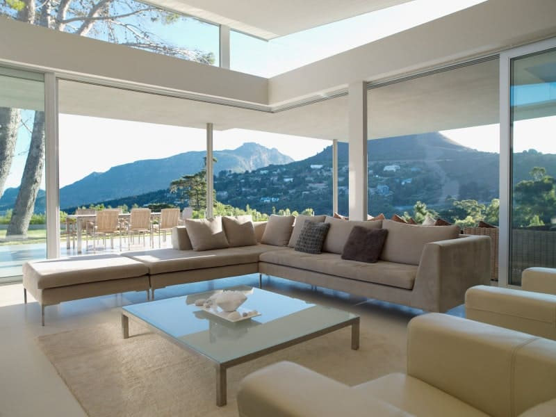 This living room boasts a panoramic window overlooking a spectacular mountain view. It includes a beige velvet sectional and a glass top coffee table.