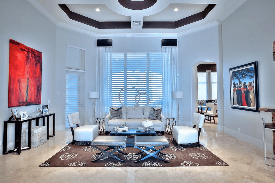 Elegant living room showcases a stylish tray ceiling and marble tiled flooring topped with a brown patterned rug. It is decorated with lovely artworks mounted on the white walls.