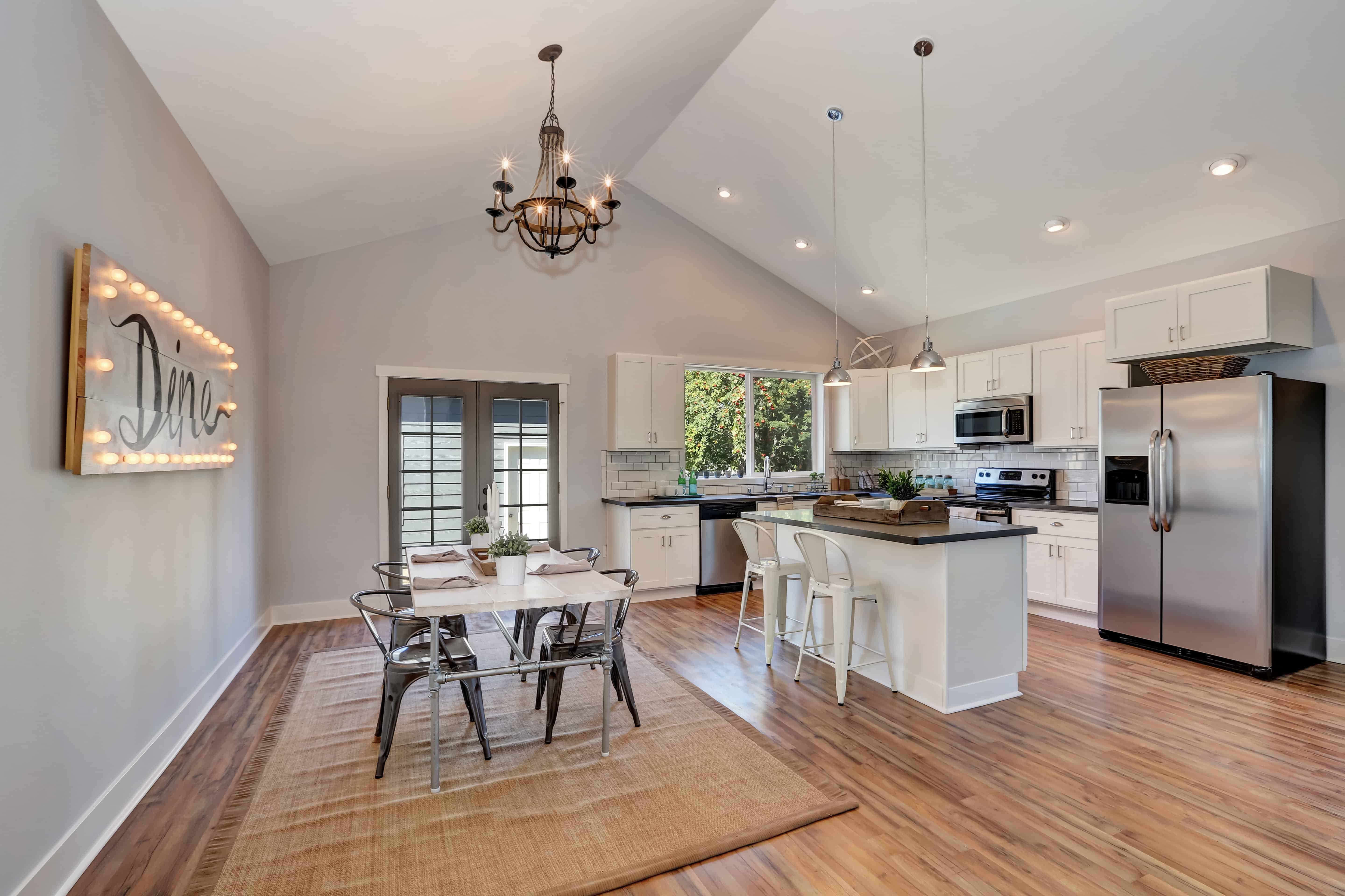 """An eat-in kitchen showcases hardwood flooring topped with a gray rug and white cathedral ceiling fitted with recessed and pendant lights. It is styled with a framed decor that says """"dine"""" surrounded with led lights."""