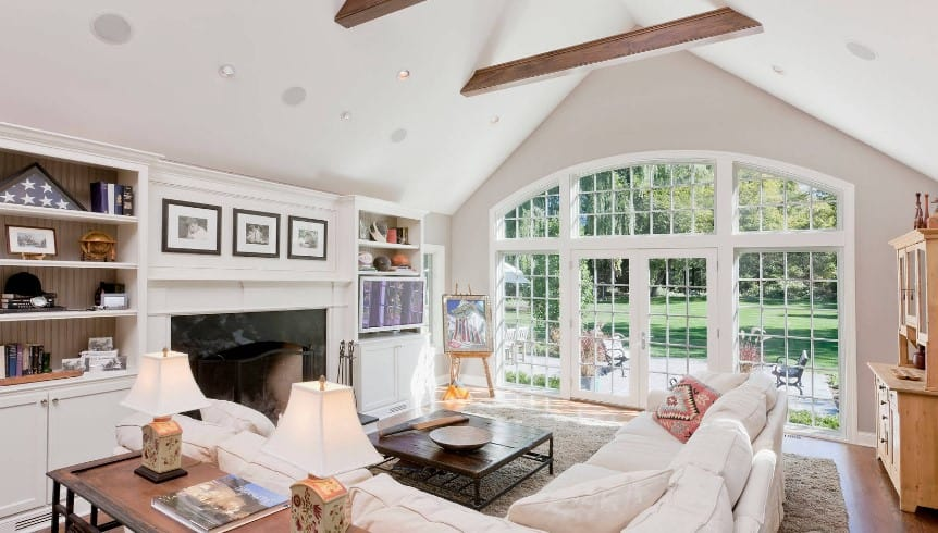 Traditional family room features an L-shaped sectional surrounding a wooden coffee table. It has a french door and windows overlooking a green outdoor view.