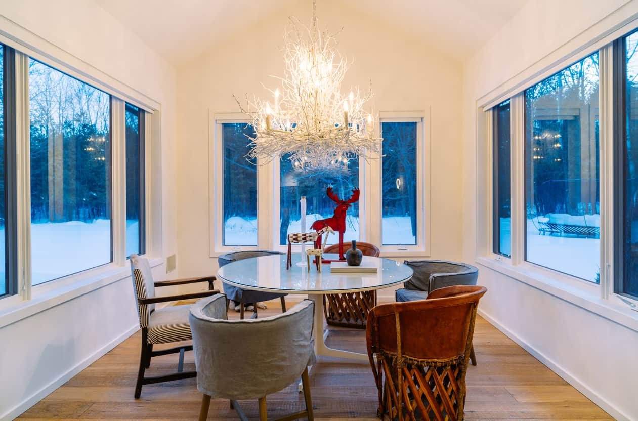 A white twig chandelier hung from a cathedral ceiling over a round glass top table with mismatched chairs in this glazed dining room.