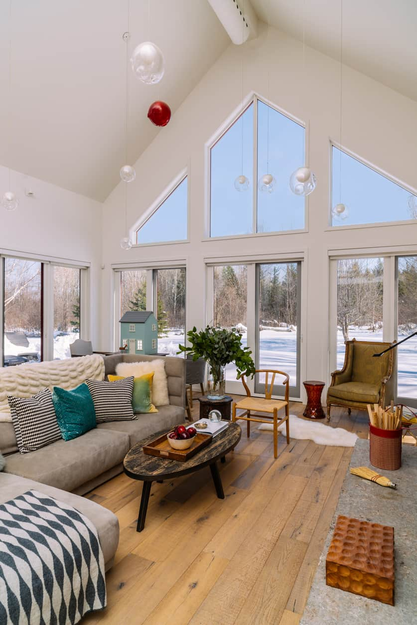 Cottage living room decorated with glass bubble pendant lights that hung from the white cathedral ceiling. It has glass windows overlooking a serene outdoor view.