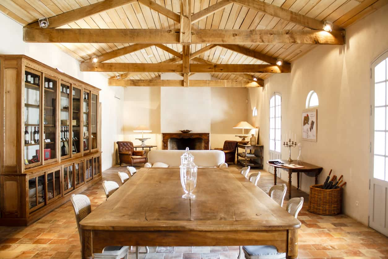 Rustic dining room features a wooden table with white chairs and bench over a brick flooring. It has a cathedral ceiling with exposed wood beams fitted with light fixtures.