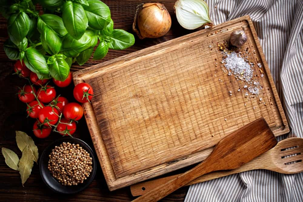 A wooden cutting board with a garlic and some salt beside onions, tomatoes, herbs, a bowl of seeds, and a pair of wooden ladles.