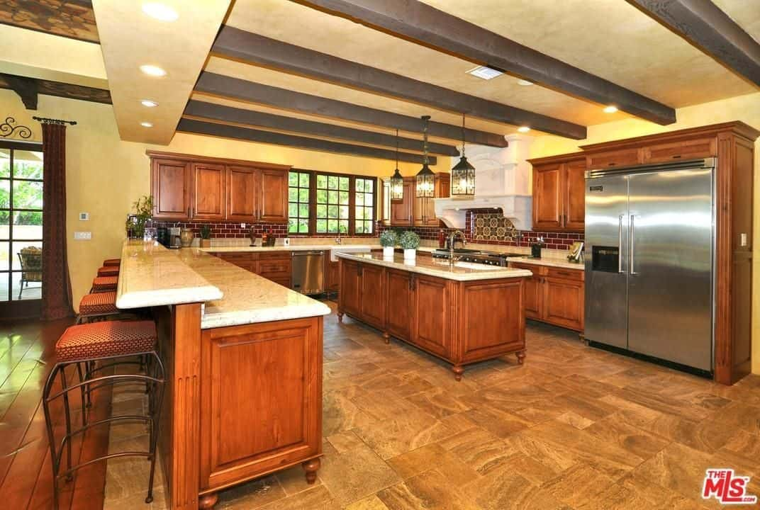The impressive beige ceiling of this spacious kitchen has exposed wooden beams that has a dark wooden tone to it. augmented by the yellow lights of the lantern-like pendant lights hanging over the beige marble countertop of the wooden kitchen island.