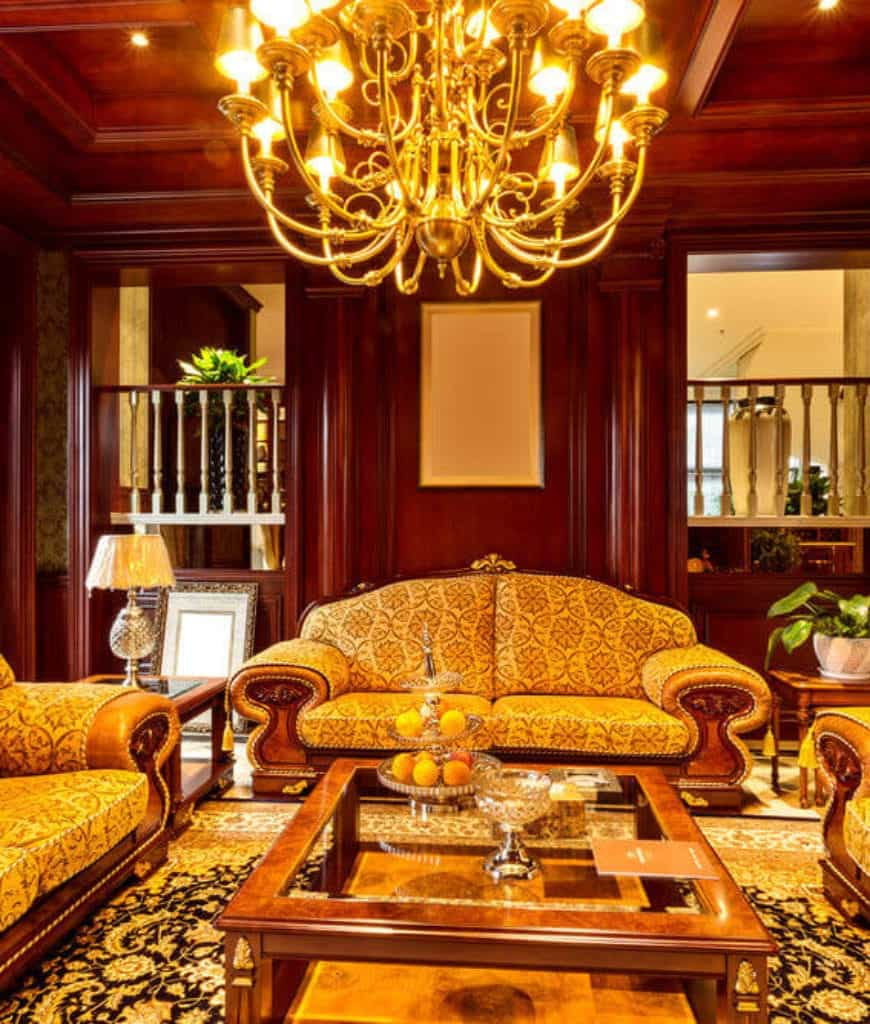 Warm living room illuminated by a brass chandelier that hung over the glass top coffee table surrounded with classy patterned couches.