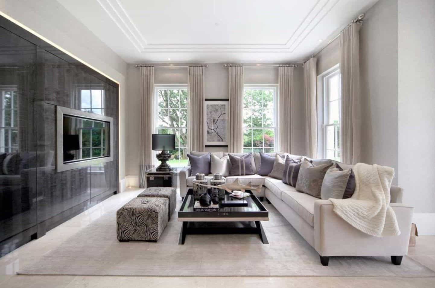 Sophisticated living room offers a wooden coffee table paired with zebra stools and an L-shaped sectional that's filled with fluffy pillows and a white throw blanket.