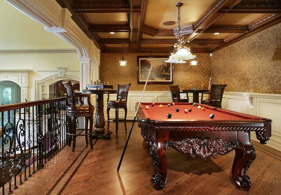 Traditional game room framed with ornate railings boasts a carved wood pool table illuminated by glass pendants that hung from the stylish tray ceiling.