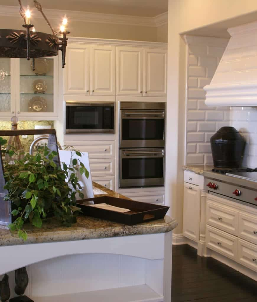 A closeup look at this kitchen with white cabinetry and range hood fixed on the subway tile backsplash. It includes stainless steel appliances inset and a round chandelier that hung over the kitchen island.