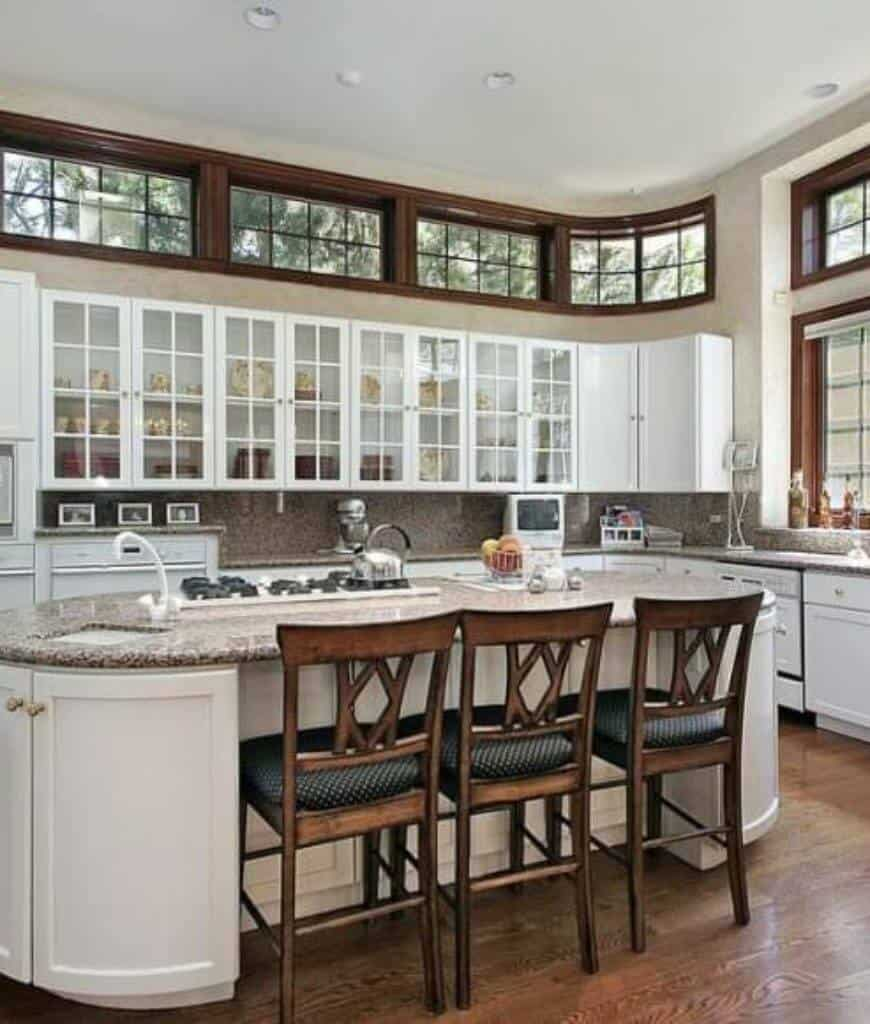 This kitchen offers glass front cabinetry and white oven. It includes a central kitchen island lined with black dotted counter chairs and fitted with a cooktop and sink.