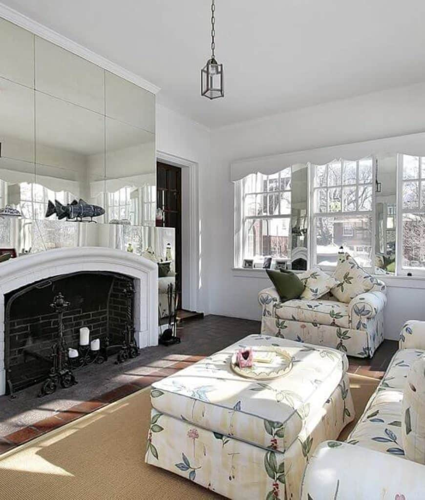 Gorgeous living room showcases a floral skirted sofa set and a black brick fireplace fixed to the mirror paneled wall lined with white crown molding.