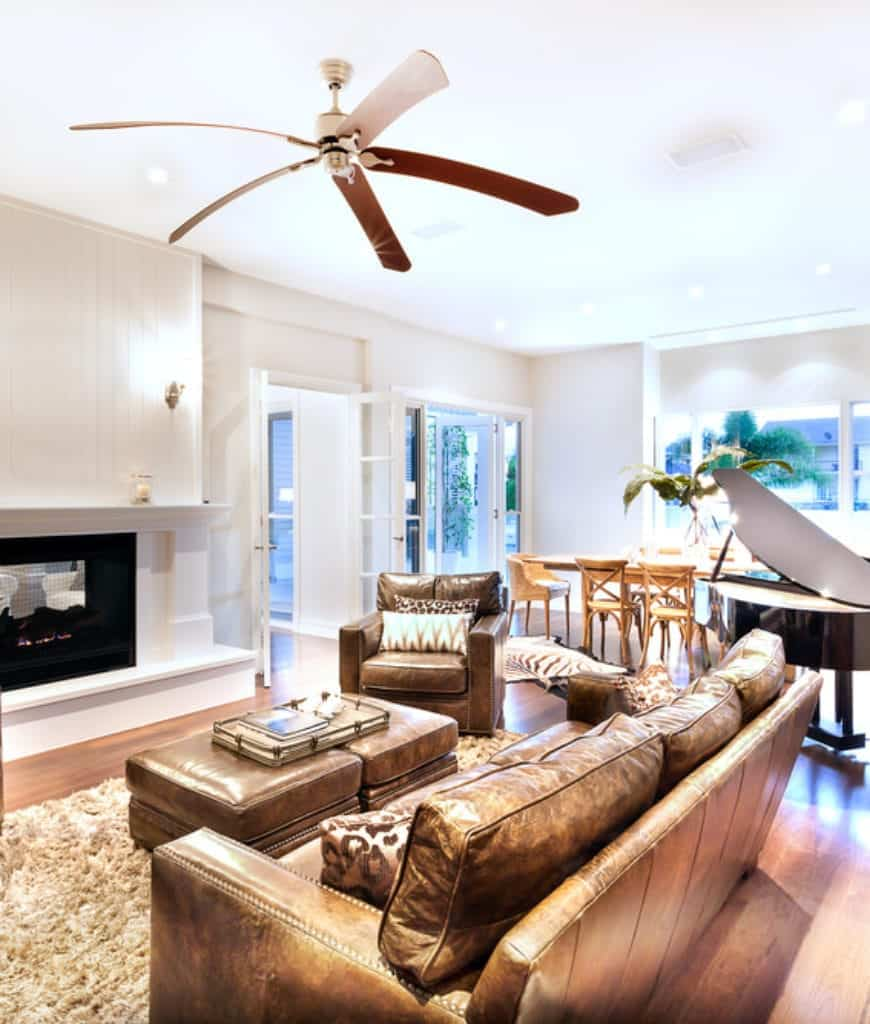 An open living room furnished with a leather sofa and armchair along with a matching ottoman over a shaggy rug facing the fireplace lighted by sconces.