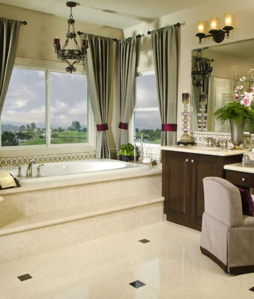 Gorgeous primary bathroom showcases a dark wood sink vanity topped with a stylish candle and vase. There's a soaking bathtub by the glass paneled windows overlooking the outdoor scenery.