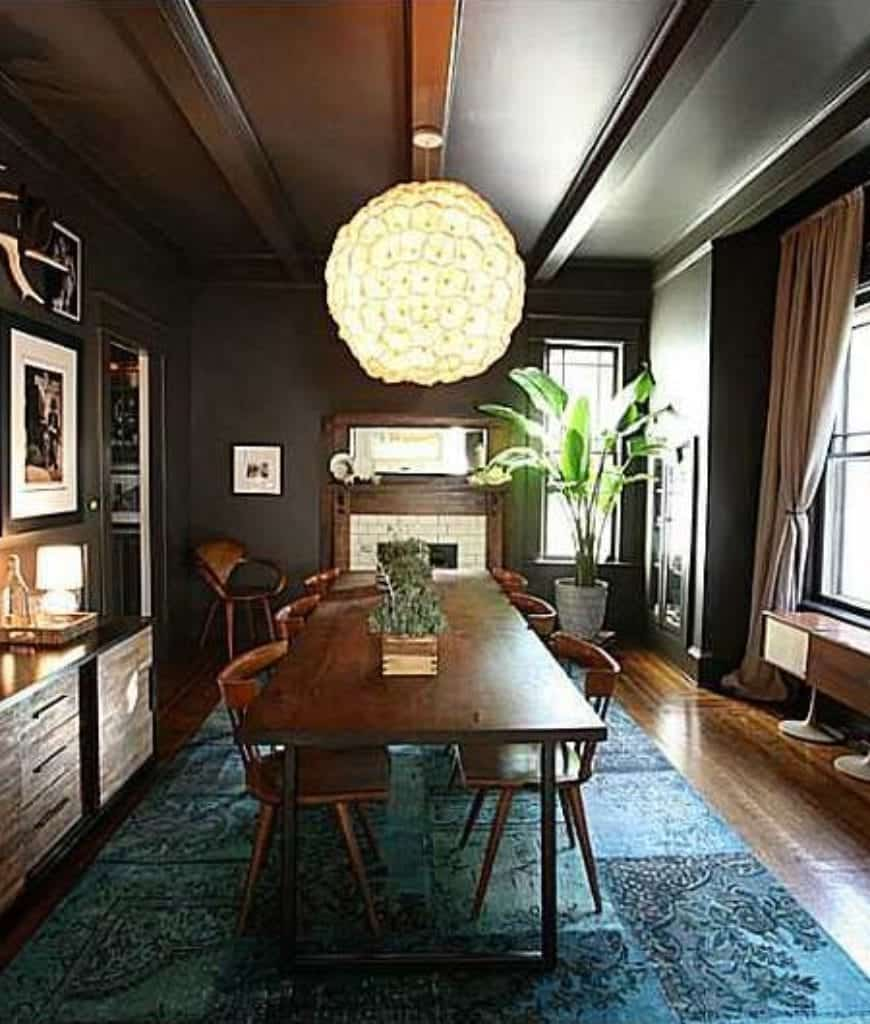 Dark dining room with gallery wall and an oversized round pendant that hung over the wooden dining table on a lovely blue area rug.