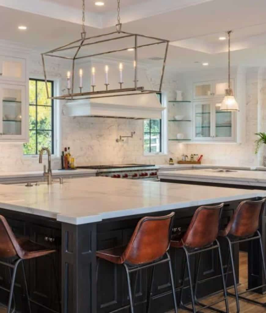 A linear chandelier is suspended over the black breakfast island in this kitchen with glass shelves and brown leather bar chairs that sit on hardwood flooring.