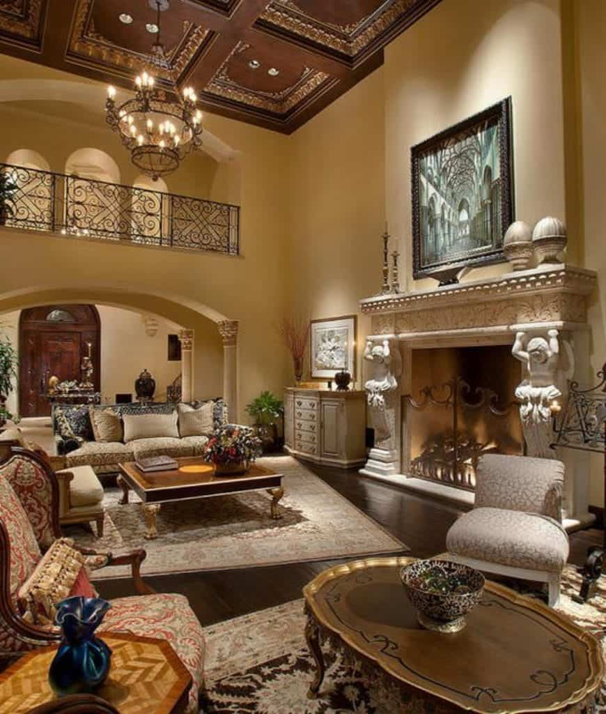 Luxury living room features dark hardwood flooring topped by vintage rugs and an ornate coffered ceiling with a hanging chandelier. It includes classy seats and a marble stone fireplace with cherub carving.