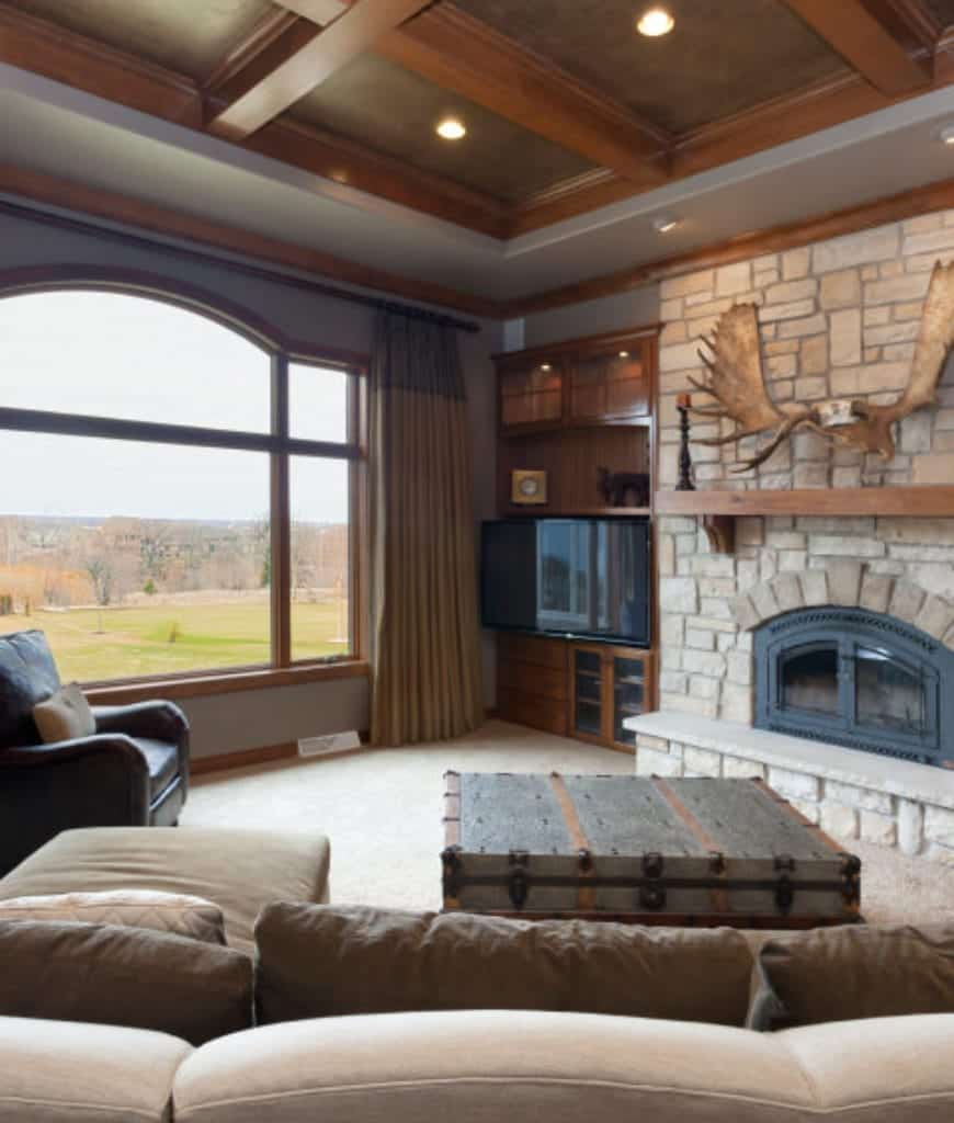 Rustic living room with wooden coffered ceiling and a stone brick fireplace lined with a natural wood mantel. There's a television in the corner adjacent to the glass paneled window overlooking a lush green outdoor view.