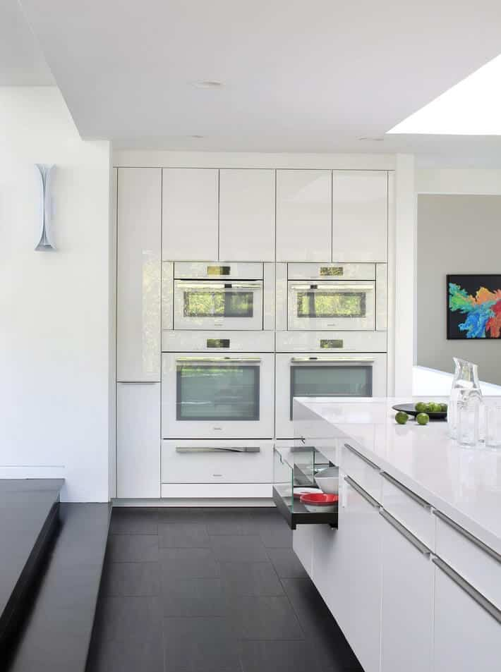 Contemporary kitchen features white appliances and cabinetry along with a sleek kitchen island fitted with a drawer and storage.