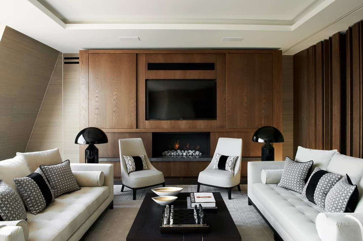 A pair of gray chairs lighted by black table lamps sit in front of the modern fireplace and television in this living room showcasing tufted sofas and dark wood coffee table.