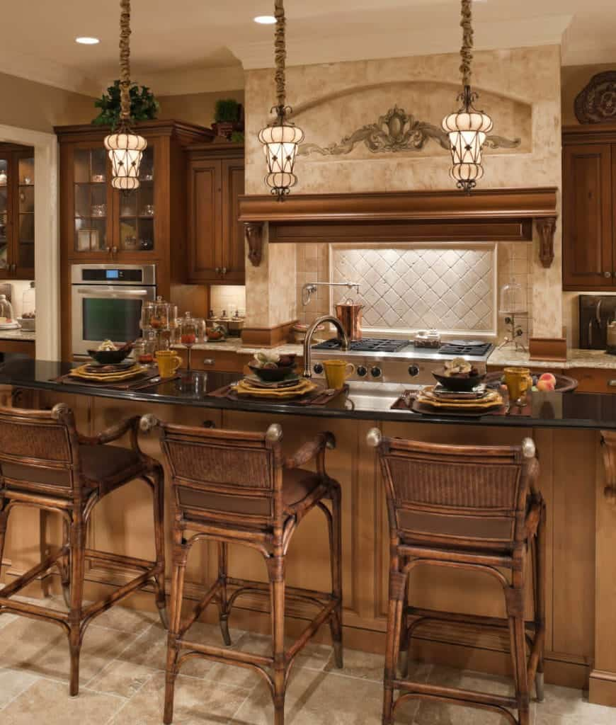 Classic kitchen showcases natural wood cabinetry and granite top breakfast island that's paired with rattan chairs and illuminated by lovely pendant lights.