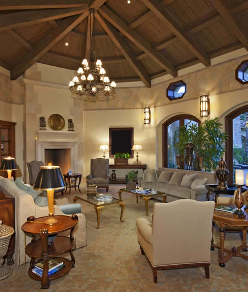 A wrought iron chandelier illuminates this living room boasting beige sofas and armchairs along with a marble fireplace accented with brass decors.