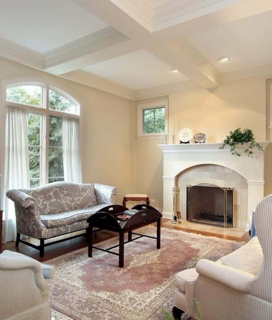 White living room with coffered ceiling and arched glass windows dressed in sheer curtains. It includes a lovely gray sofa and traditional fireplace enclosed in glass.