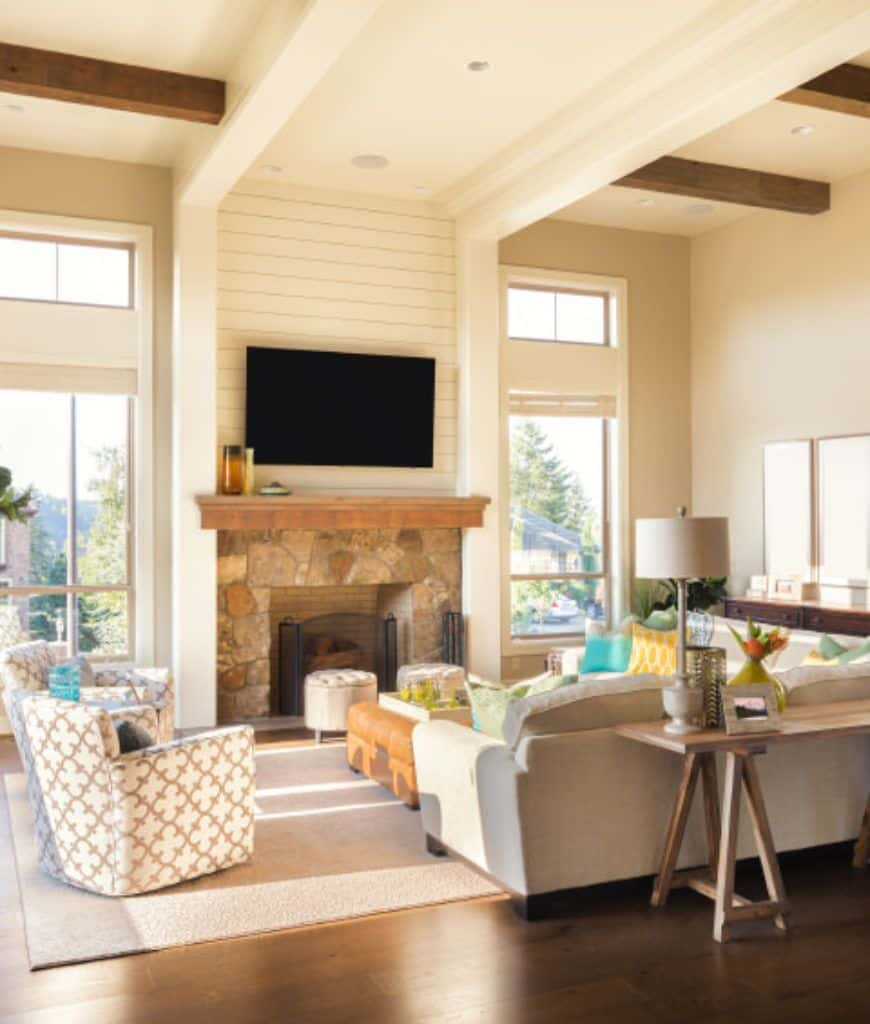 An airy living room showcases a flat panel TV mounted on the shiplap accent wall above a stone fireplace that's lined with a wooden mantel.