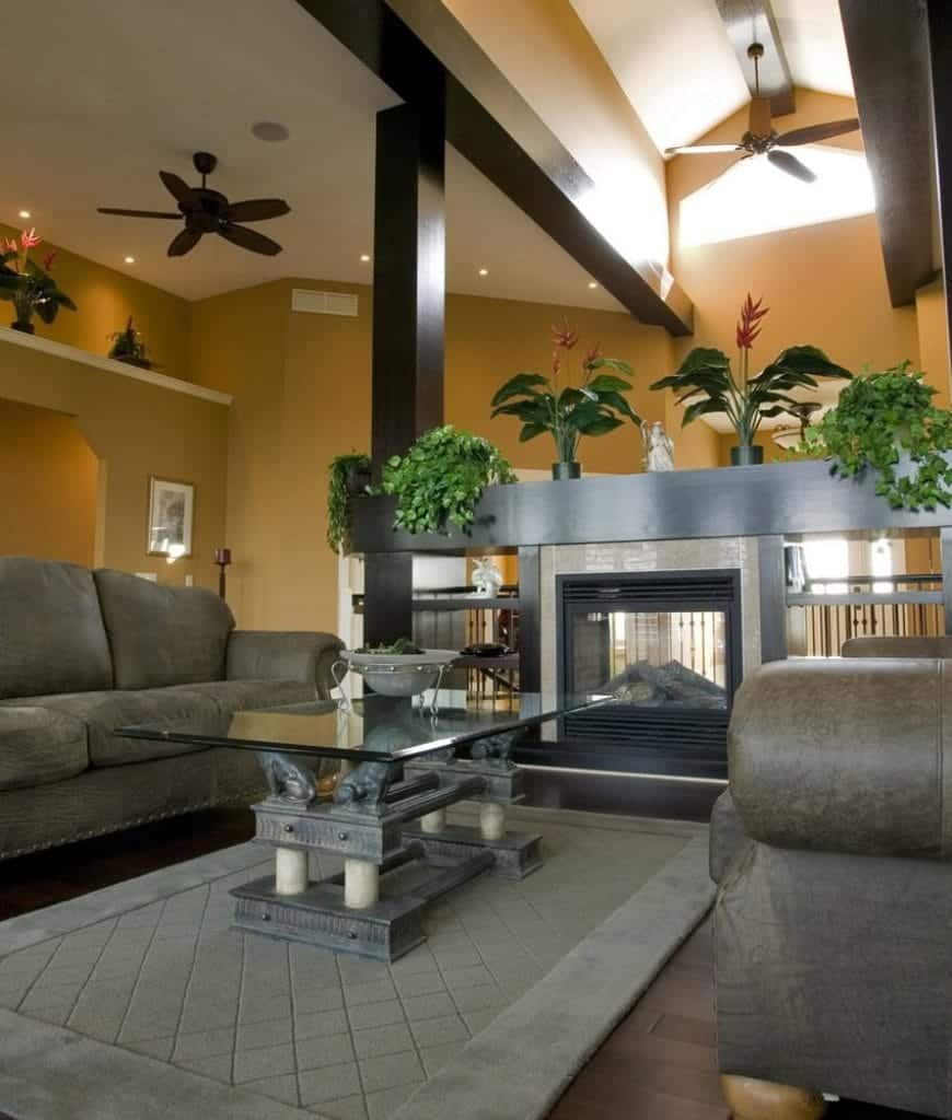 Tropical living room features gray sectionals and a glass top coffee table facing the fireplace enclosed in glass. It is fitted on wooden built-in cabinet with open shelvings.