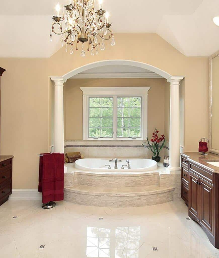 A stainless steel towel rack sits in front of the bathtub placed in an alcove in this primary bathroom that's illuminated by a fabulous chandelier.