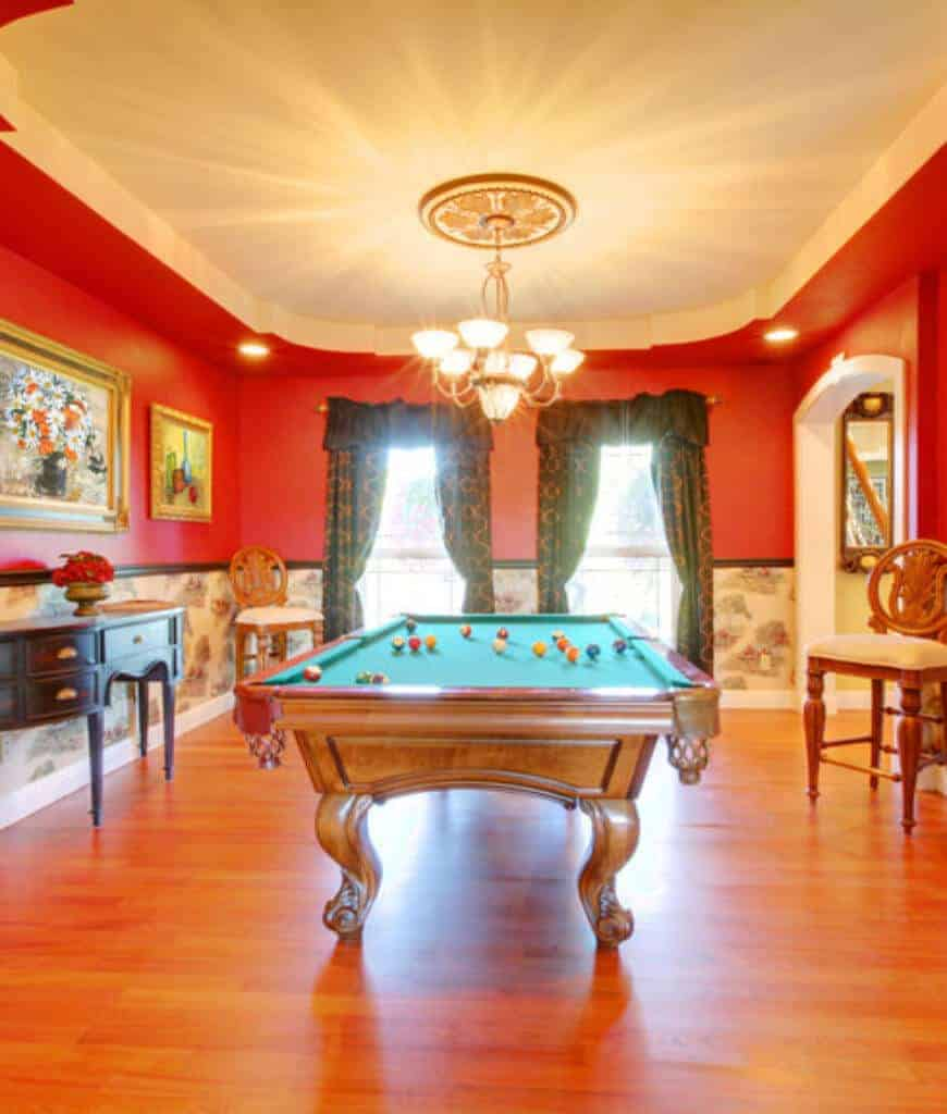A clawfoot pool table is the focal point in this red classic room lighted by a chandelier that hung from the tray ceiling. It is accompanied by a dark wood console table and round back chairs over the hardwood flooring.