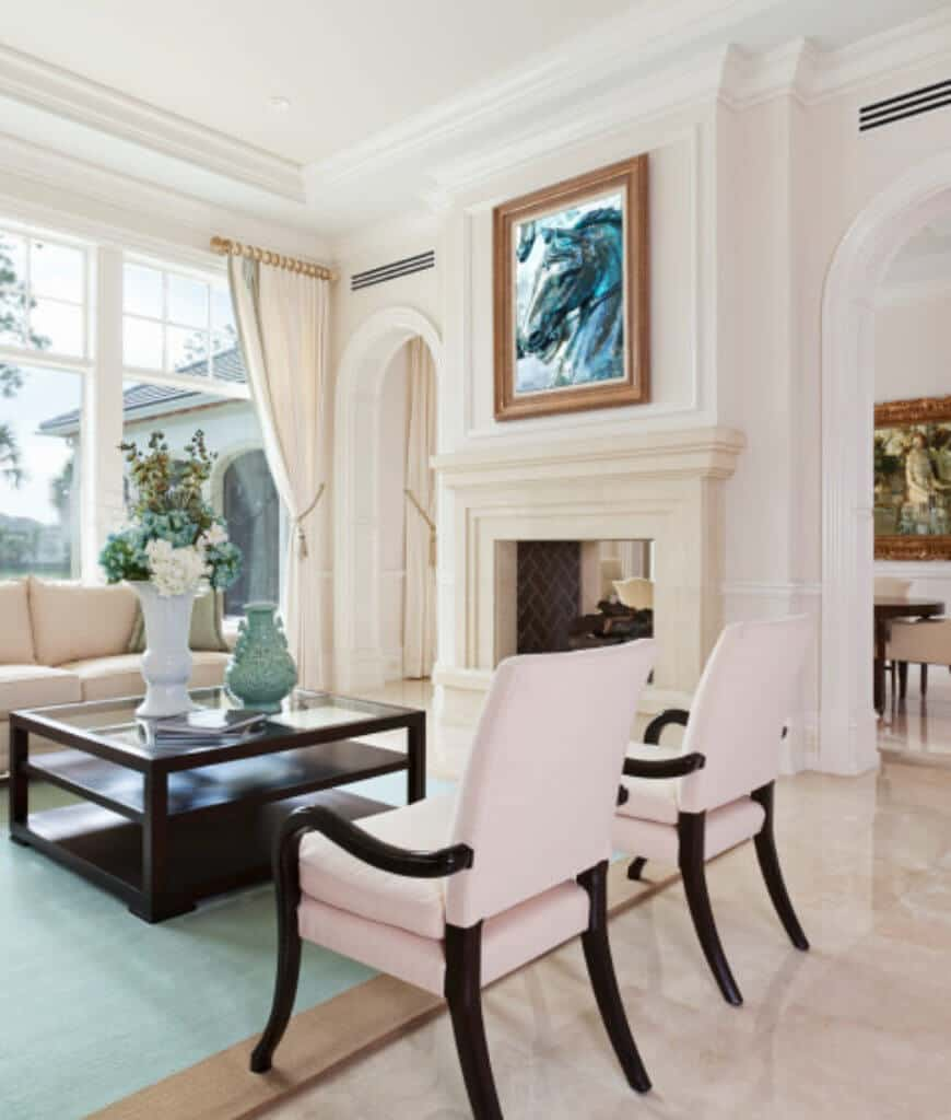 Elegant white living room with marble flooring and full height windows covered with white draperies. There's a fireplace in between open archways accented with a gorgeous horse wall art.