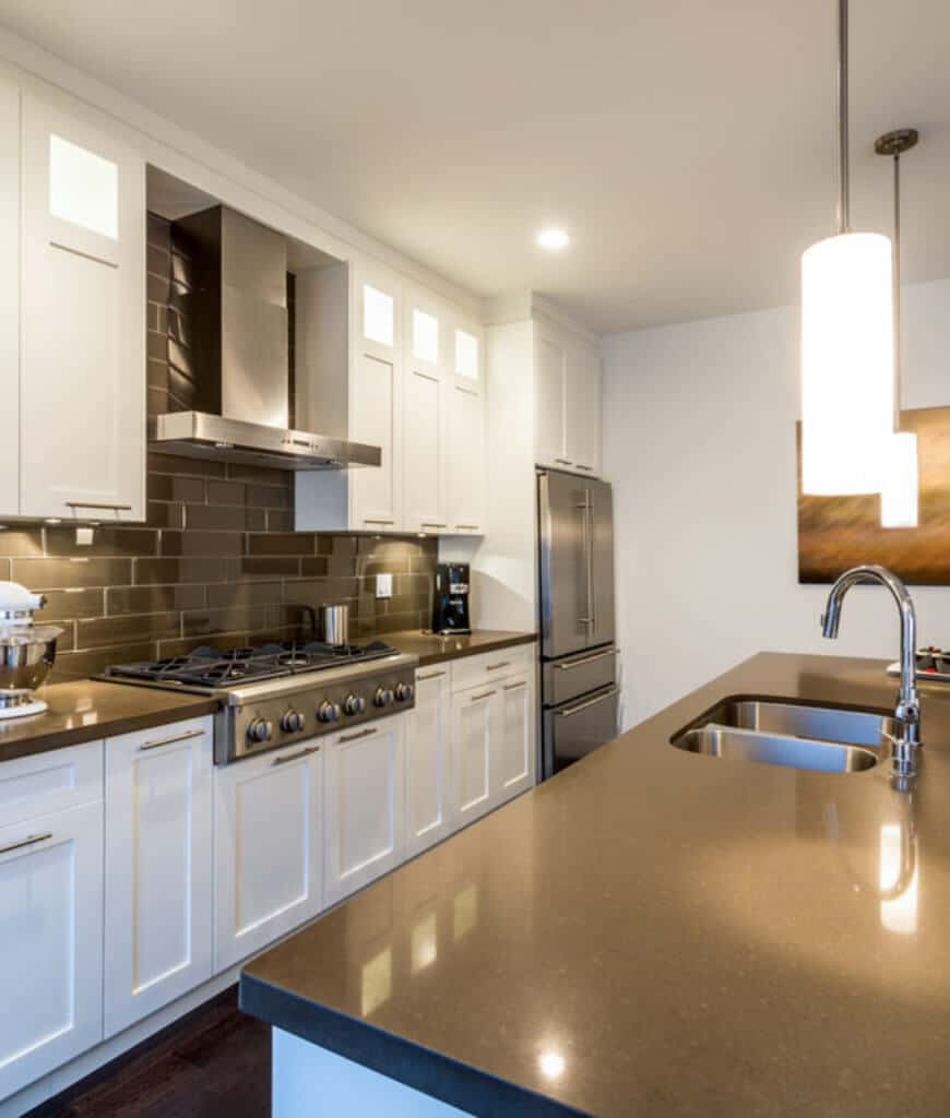 Modern kitchen with white cabinetry contrasted by black subway tile backsplash and granite countertops. It includes stainless steel appliances and cylindrical pendants that hung over the kitchen island.