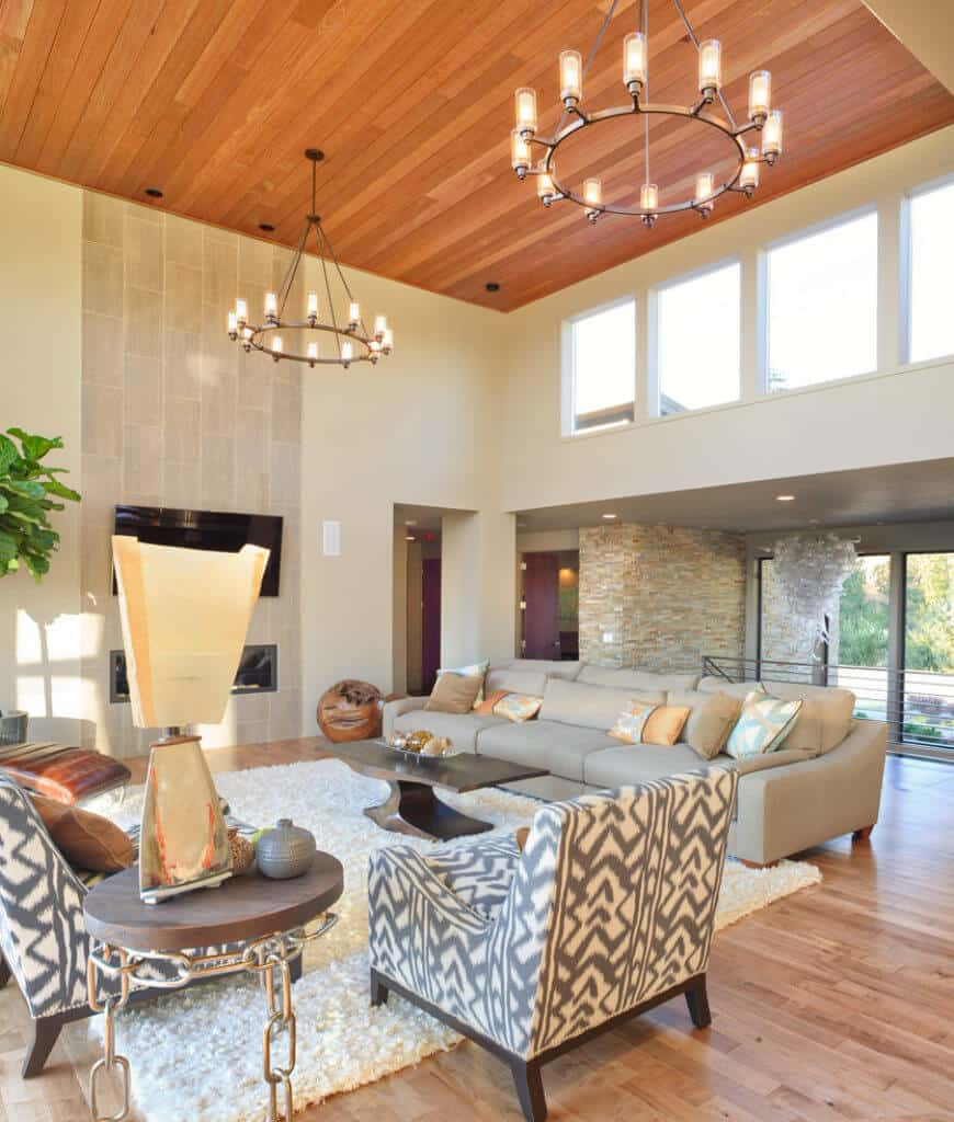 A pair of round chandeliers illuminate this living room with gray sectional and armchairs along with a wooden coffee table that sits on a white shaggy rug over wood plank flooring.