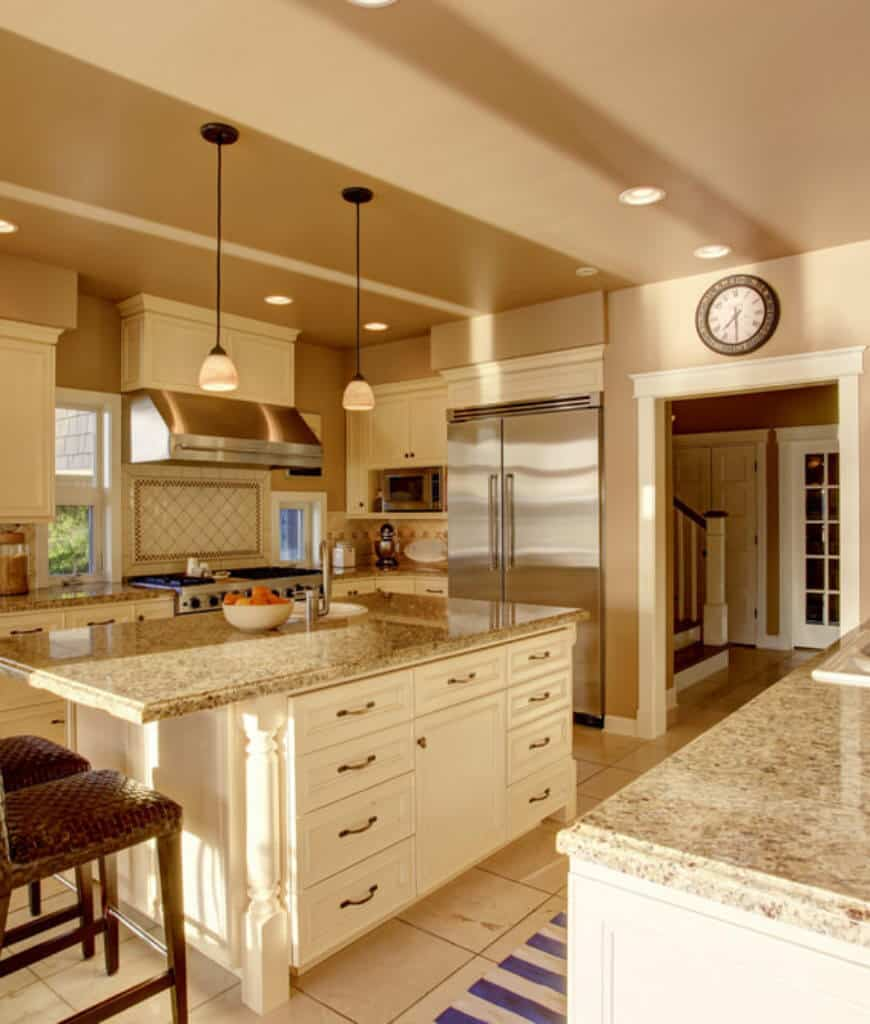 The low ambient light from the dome pendant and recessed ceiling lights create a warm and cozy vibe in this kitchen.