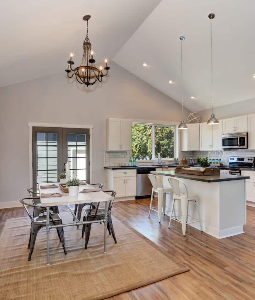 Spacious eat-in kitchen with a white central island lighted by a pair of chrome pendants along with a metal dining set that sits on a wicker area rug over wood plank flooring.
