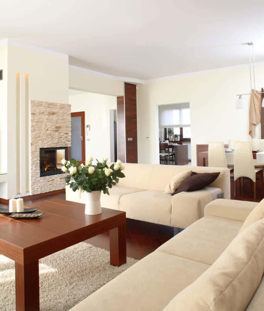 An open living room features beige sectionals and a wooden coffee table that sits on a shaggy rug. There's a double-sided fireplace fixed to the cream wall clad in stone brick tiles.