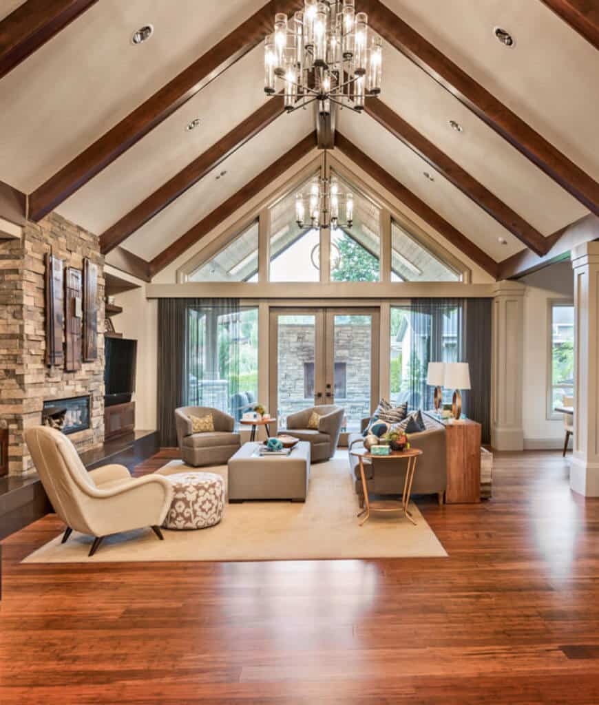 Craftsman living room offers full height glazing and cathedral ceiling fitted with wood beams and a hanging glass chandelier. It includes a brick fireplace and smooth beige rug that lays on the rich hardwood flooring.