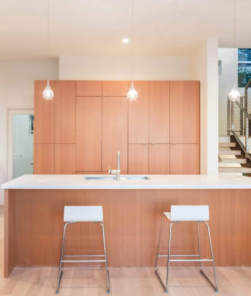 Sleek kitchen with wooden cabinetry and matching breakfast island that creates a cohesive look. It is paired with white bar stools and lighted by drop pendant lights.