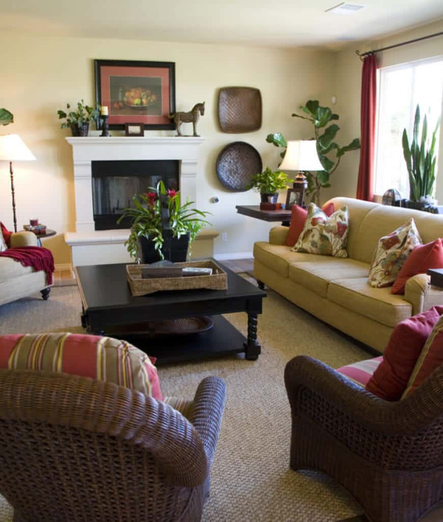 Red and floral pillows lay on the tan sectional in this living room with a fireplace and wicker round back chairs fitted with striped cushions.