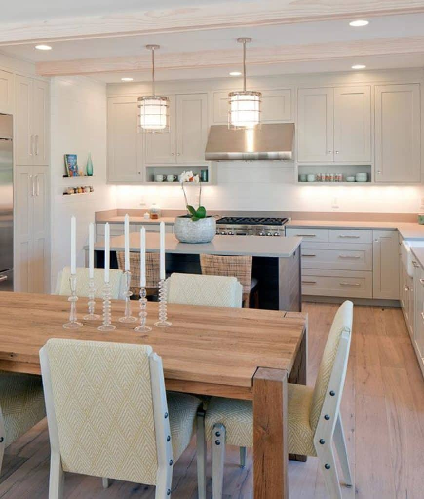 Stylish eat-in kitchen boasts an island bar illuminated by a pair of pendant lights along with a wooden dining table surrounded with gorgeous chairs and topped with glass candle holders.