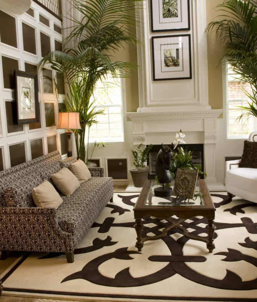 Gorgeous living room boasts a patterned sofa and glass top coffee table that sits on a beige rug. It includes a white fireplace accented with plants and black framed wall art.
