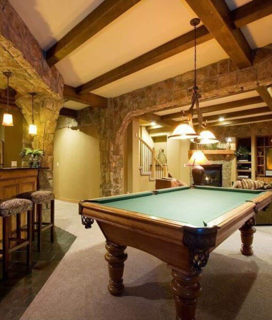 Marvelous family home accented with bricks and wood beams showcases a pool table in between bar area and living space with fireplace.