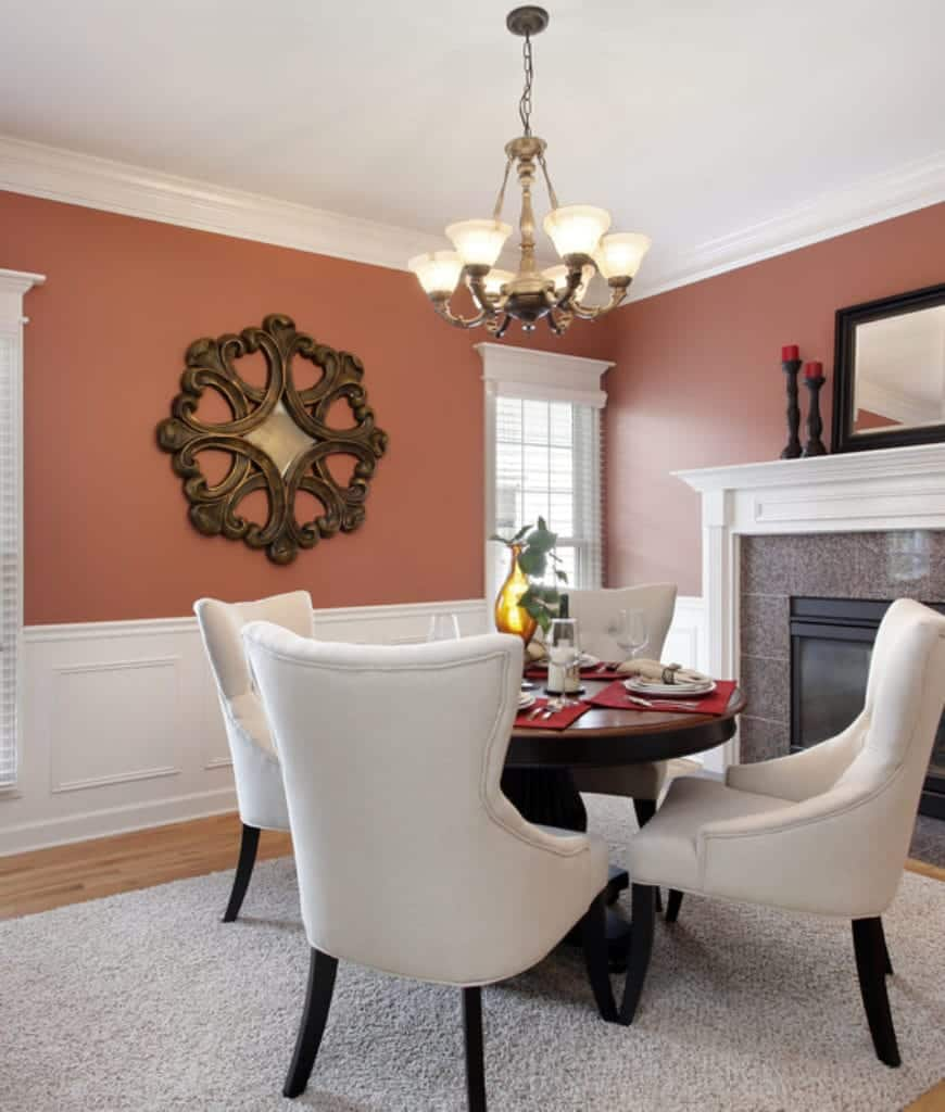 Gorgeous dining room decorated with a round carved wood wall art mounted above the white wainscoting. It has a wooden dining table and white wingback chairs on a gray rug over the light hardwood flooring.