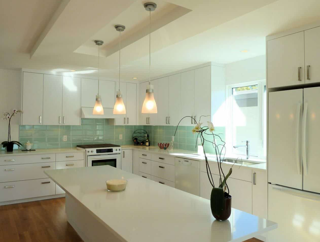 Modern kitchen showcases a central breakfast island lighted by glass pendants that hung from the tray ceiling. It is surrounded with white appliances and cabinetry accented with mint green backsplash tiles.