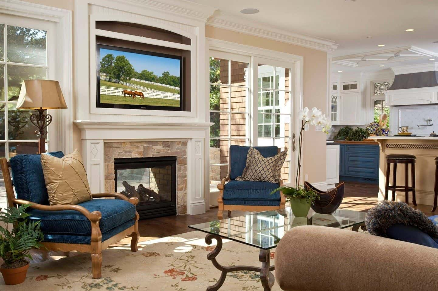 Gorgeous living room accented with blue armchairs that faces the glass top coffee table and sofa. It includes a television that hung above the fireplace with stone surround tiles.